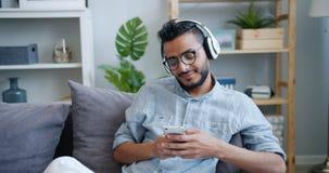 Handsome Arabian guy using smartphone listening to music in headphones at home. Handsome Arabian guy is using smartphone and listening to music in headphones stock footage