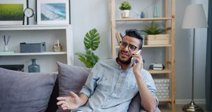 Handsome Arabian man chatting on mobile phone laughing on sofa at home. Handsome Arabian man student is chatting on mobile phone laughing sitting on sofa at home stock footage