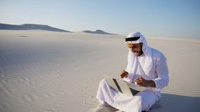 Handsome Arabian UAE Sheikh guy businesswoman calling business p. Smart handsome emirate Arabian UAE Sheikh businessman prints on computer keyboard and answers stock image