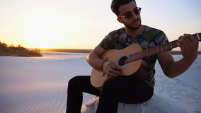 Handsome Arabian young man adjusts guitar, sitting on hill in middle of desert at sunset in open air on warm evening. Ambitious budding musician, Muslim guy stock video footage