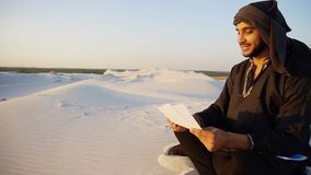 Handsome arabic male architect looks at documents and sits on sa. Educated male Muslim builder or designer works with drawings and inspects terrain for future Royalty Free Stock Images