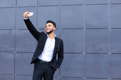 Handsome arabic man takes selfie smart phone in business center Stock Photos