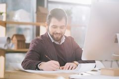 Handsome architect drawing blueprint at workplace. With computer stock photography