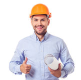 Handsome architect in helmet. Handsome architect in classic shirt and protective helmet is holding rolled paper, showing Ok sign, looking at camera and smiling royalty free stock images