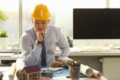 Handsome Architect Interior Blueprint Renovation. House Drafting Concept. Busy Engineer Sit at Workplace, Analyze Contractor Project. Businessman Think Wearing stock photo