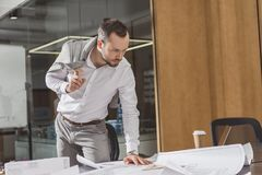 Handsome architect looking at building plans on desk. At office royalty free stock image