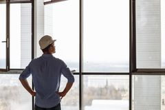 Handsome architect looking forward is standing a white helmet. Back view photo. the end of a working day royalty free stock photos