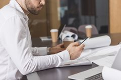 Handsome architect with paper cup of coffee using smartphone. At office royalty free stock photo