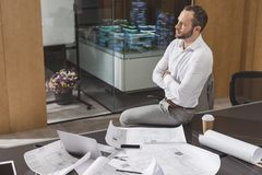 Handsome architect sitting on table with crossed arms. At office stock image