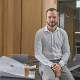 Handsome architect sitting on table with plans. At office stock photography