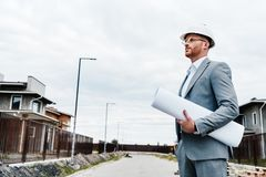 Handsome architect in suit and hard hat holding blueprint looking. At building house royalty free stock image