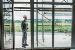 Handsome architect in suit and hard hat standing on terrace. At construction site royalty free stock photo