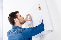 Handsome architect writing on blueprint. On white stock photography