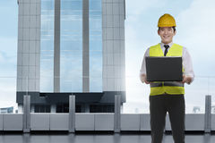 Handsome asian architect man with laptop wearing protective helm Stock Photo