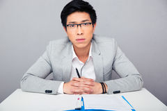 Handsome asian businessman in glasses sitting at the table with pen a Stock Photos