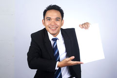 Handsome asian businessman holding a blank paper with pointing gesture. Photo Image of handsome asian businessman holding a blank paper with pointing gesture Stock Photos