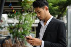 Handsome Arab Asian businessman with smartphone. Young smart Arab Asian businessman check project plan and chat with coworkers on mobile smartphone by 4g stock images