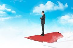 Handsome asian businessman standing on paper plane flying. With cloud and blue sky background. Business concept stock photos