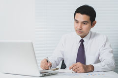 Handsome Asian businessman working in the office with laptop com Stock Photos