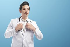 Handsome asian doctor man wearing lab coat and holding stethoscope on his neck stock photos