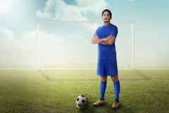 Handsome asian football player with arm crossed standing Royalty Free Stock Images