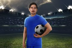 Handsome asian football player with soccer ball. On the stadium field Stock Images