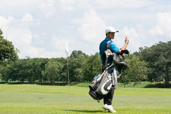Handsome asian golf player man with his bag on golf course with Royalty Free Stock Photo