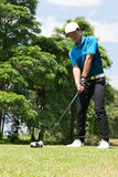 Handsome asian golfer man putt golf . Stock Photos