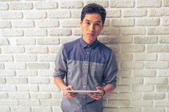 Handsome Asian guy with gadget. Handsome Asian guy is holding a tablet and looking at camera while standing against white brick wall royalty free stock photography