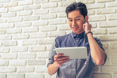 Handsome Asian guy with gadget Royalty Free Stock Images