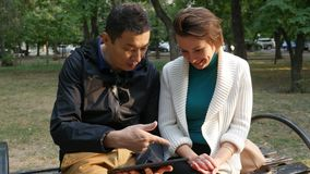 Handsome asian guy holding touch screen tablet with Caucasian girl in the park. Happy romantic Couple of Young Man and Woman Sitting on bench at the park Using stock video footage