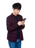 Handsome asian guy sit and read message on his smartphone Royalty Free Stock Image