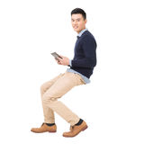 Handsome Asian guy sit and use pad. Full length portrait isolated on white background royalty free stock image