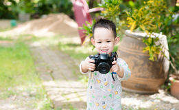Handsome Asian kid take a photo by digital camera Royalty Free Stock Image