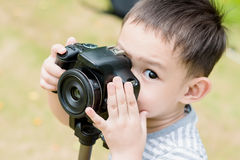 A Handsome Asian kid take a photo by DSLR camera Royalty Free Stock Image