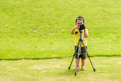 Handsome Asian kid take a photo by DSLR camera Stock Image
