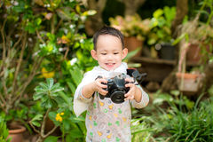 Handsome Asian kid take a photo by DSLR camera Stock Photo
