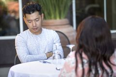 Handsome Asian Male on a Date with a Female Outdoors. Handsome asian men on an outdoor date with a black female.  The couple are sitting in a restaurant or cafe Stock Photography