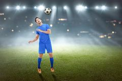 Handsome asian male football player trying to heading the ball stock photos