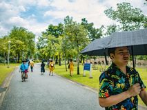 Handsome Asian male wear hawai t -shirt Holding umbrella and walking in the Chatuchak park stock image