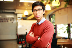 Handsome asian man with arms folded standing Royalty Free Stock Photos