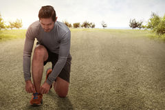 Handsome asian man kneeling tying running shoes getting ready fo Royalty Free Stock Photo