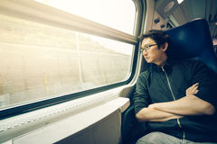 Handsome asian man looking through train window, warm light tone, with copy space.  Stock Photos