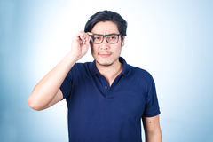 Handsome Asian man looking up while holding glasses with hand, o Royalty Free Stock Images