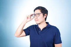 Handsome Asian man looking up while holding glasses with hand, o Royalty Free Stock Photo