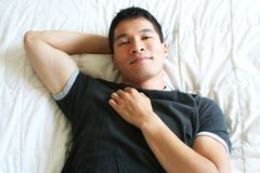 Handsome Asian Man resting. Handsome, Asian male model resting on mattress with gray tee shirt Royalty Free Stock Photography
