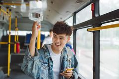Handsome asian man sitting in city bus and typing a message  Stock Images