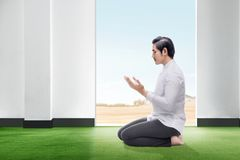 Handsome asian man sitting in praying position close his eyes and raise the hands on the carpet inside the room stock image