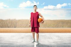 Handsome asian man with sport uniform carrying the ball royalty free stock photos