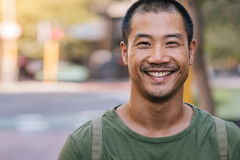 Handsome Asian man standing on a city street and smiling. Close up portrait of a casually dressed handsome young Asian man smiling while standing alone outside Royalty Free Stock Photos